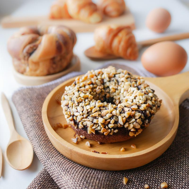 Homemade food fresh bakery, Closeup delicious chocolate donut almond peanut topping served on wooden dish, spoon, fork on napery stock images