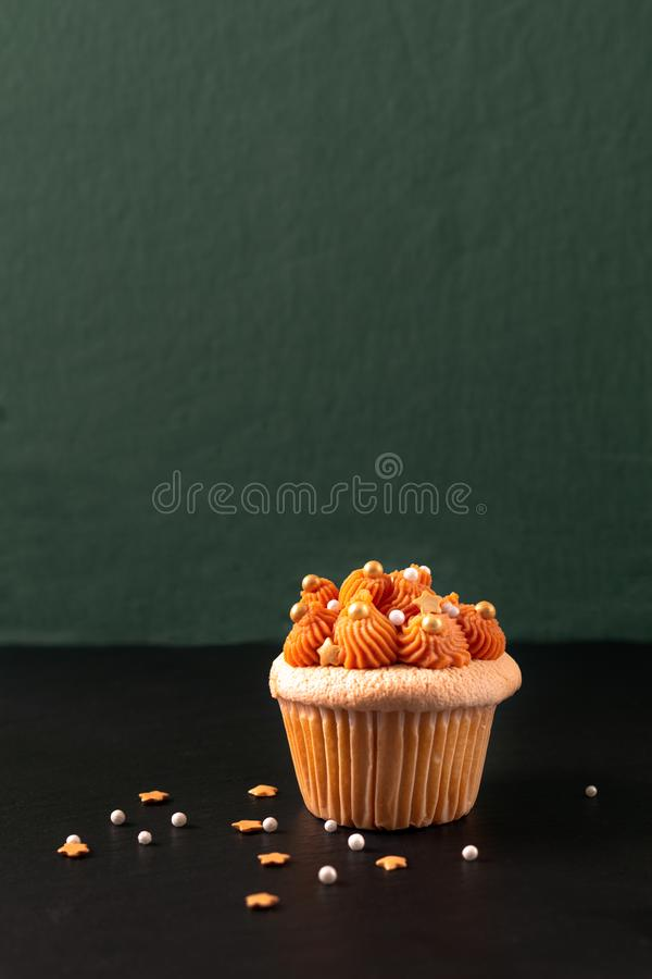 Homemade food Thai ice tea cupcake on black slate board and green background with copy space royalty free stock images