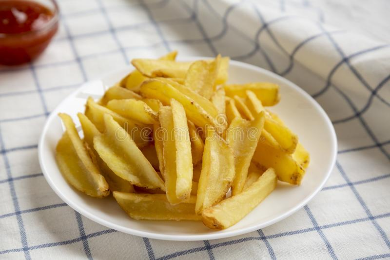 Homemade french fries with sour-sweet sauce on a white plate, low angle view. Closeup.  stock images