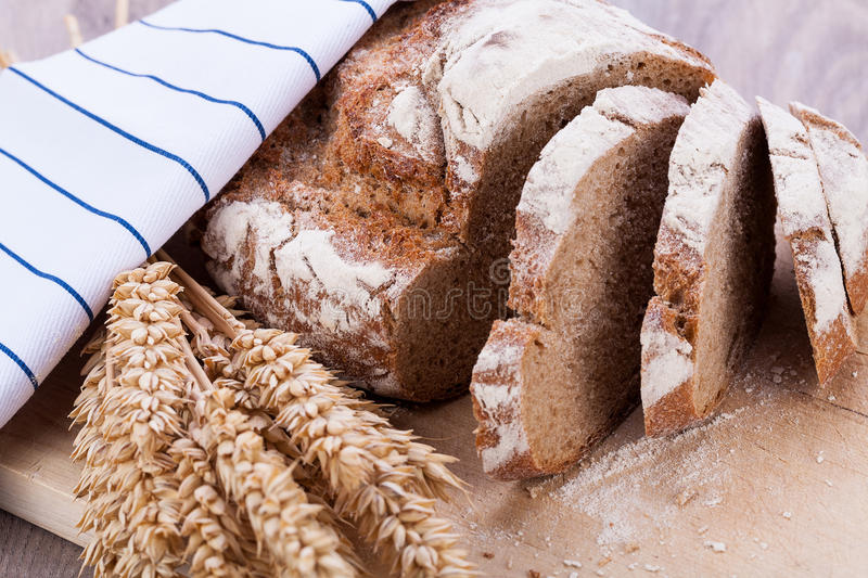 Homemade fresh baked bread and knife. On wooden table royalty free stock photography