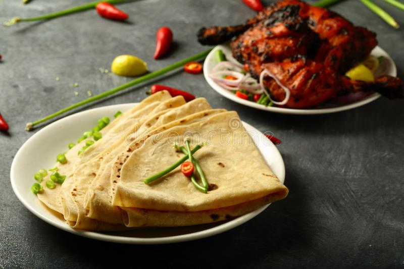 Homemade fresh chapati with tandoori chicken. Delicious homemade chapathi,capati with tandoori chicken on a dark background. famous Indian recipe royalty free stock image