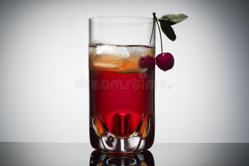 Homemade fresh cherry juice in transparent glass with ice and fresh cherry. Gradient background. royalty free stock photography