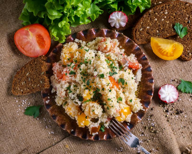 Homemade Fresh Couscous salad with tomatoes in plate stock photo