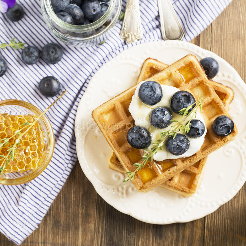 Homemade fresh crispy waffles for breakfast with blueberries. Homemade fresh crispy waffles for breakfast with fresh blueberries and honey on a ceramic bowl and stock photography