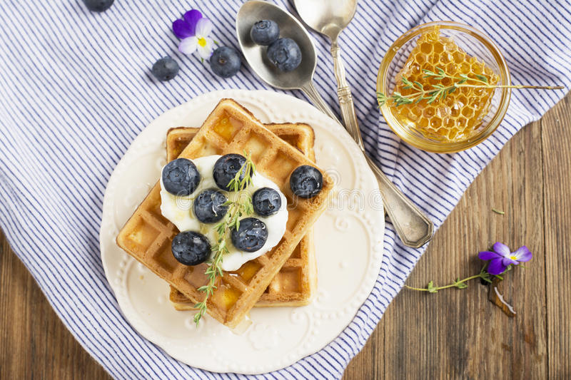 Homemade fresh crispy waffles for breakfast with blueberries. Homemade fresh crispy waffles for breakfast with fresh blueberries and honey on a ceramic bowl and royalty free stock photography