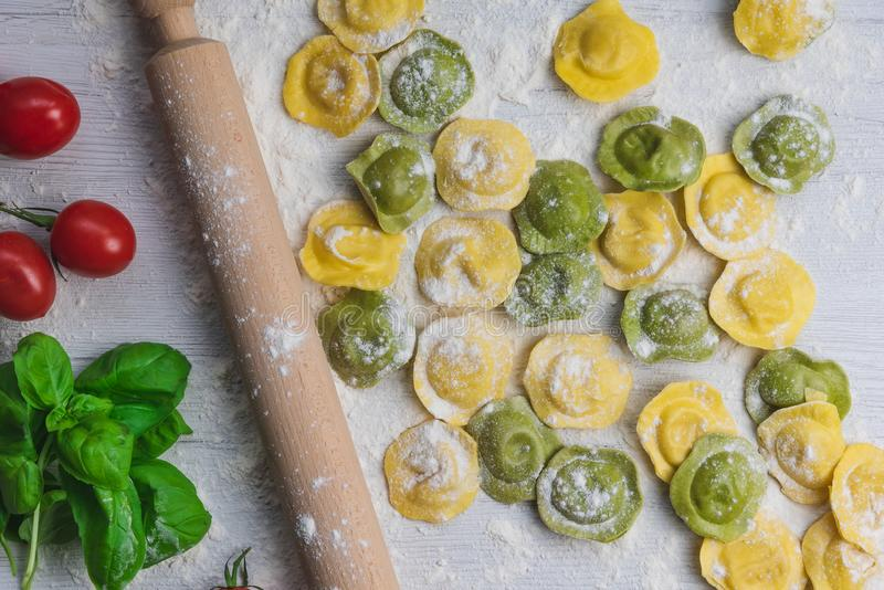 Homemade fresh Italian ravioli pasta on white wood table with flour, basil, tomatoes,background,top view royalty free stock image