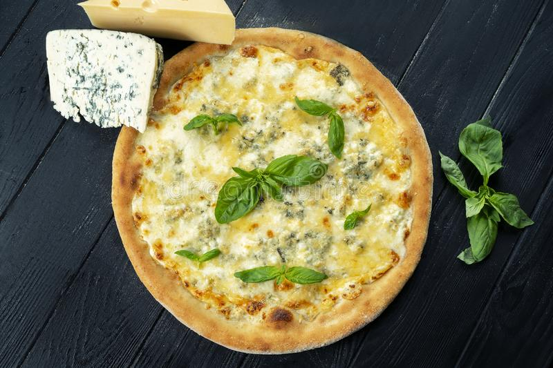 Homemade fresh Pizza with four cheese and basil on a black wooden with copy space. Top view food photo. Flat lay. Italian cuisine royalty free stock image