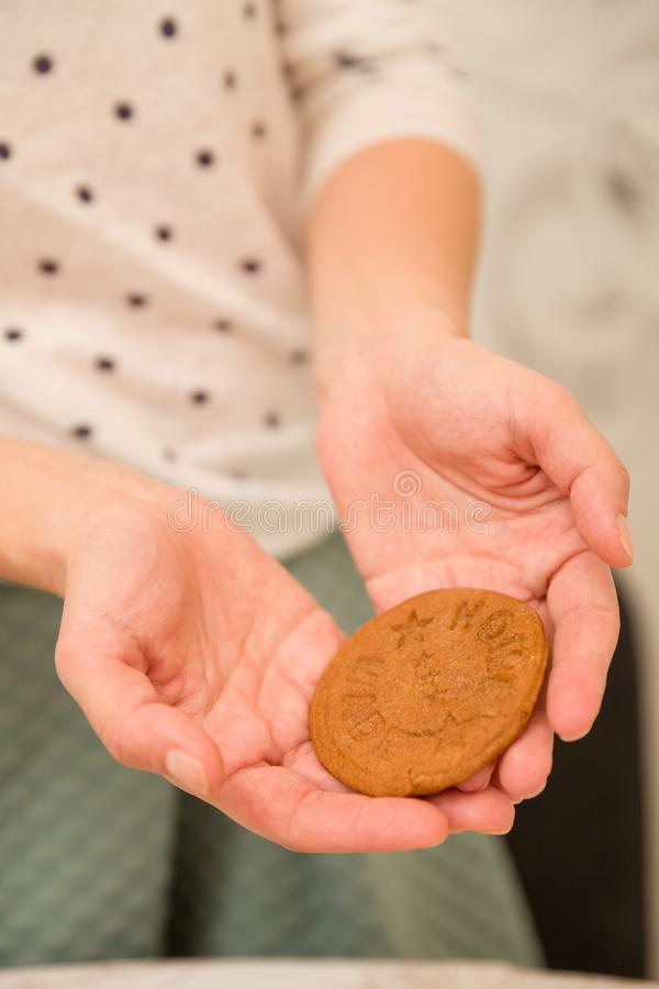 Homemade fresh round cookie in hands of a woman in green skirt and white sweater. Baking biscuits at home. royalty free stock photo