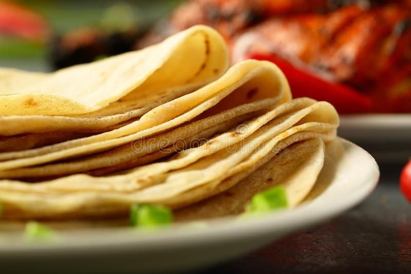 Homemade fresh whole wheat chapati ,. Delicious homemade chapathi,capati on a dark background. famous Indian recipe,with tandoori chicken,salads stock photos