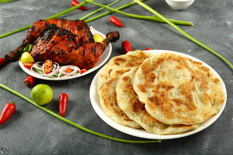 Homemade fresh whole wheat parataha,Indian cuisine. Delicious homemade parataha,roti,nan on a dark background. famous Indian recipe,with tandoori chicken,salads royalty free stock photos