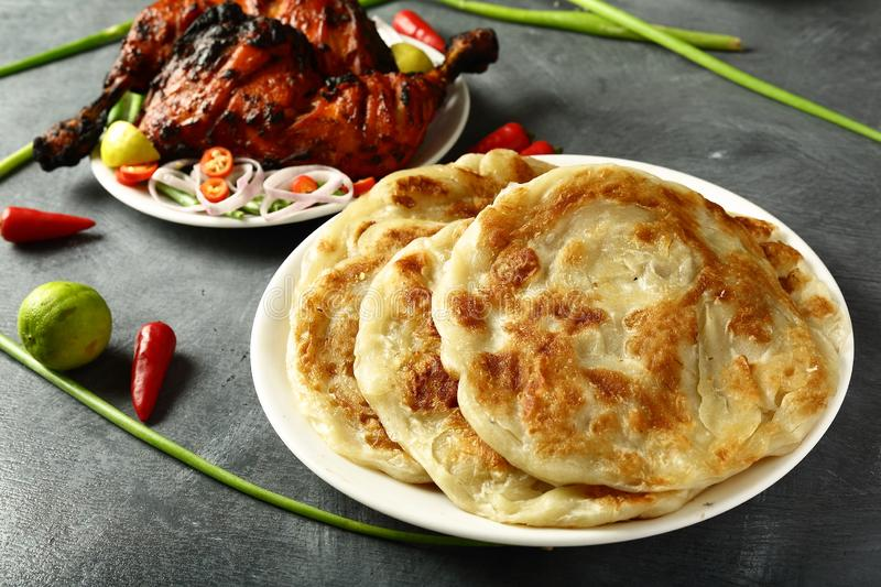 Homemade fresh whole wheat parataha,Indian cuisine. Delicious homemade parataha,roti,nan on a dark background. famous Indian recipe,with tandoori chicken,salads stock photos