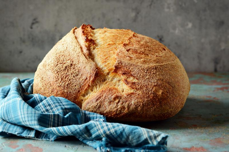 Homemade Freshly Baked Country Bread made from wheat and whole grain flour on a gray-blue background. royalty free stock photo