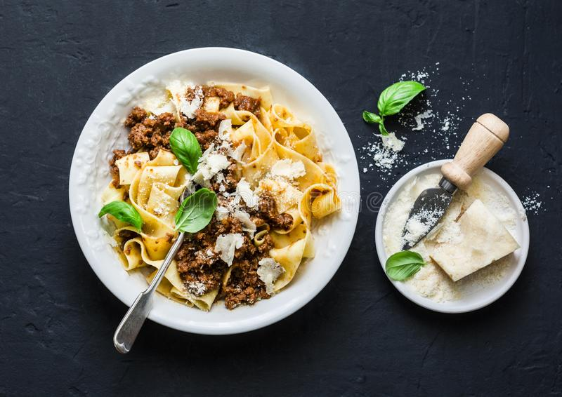 Homemade freshness pappardelle pasta with beef bolognese sauce on a dark background. stock photos