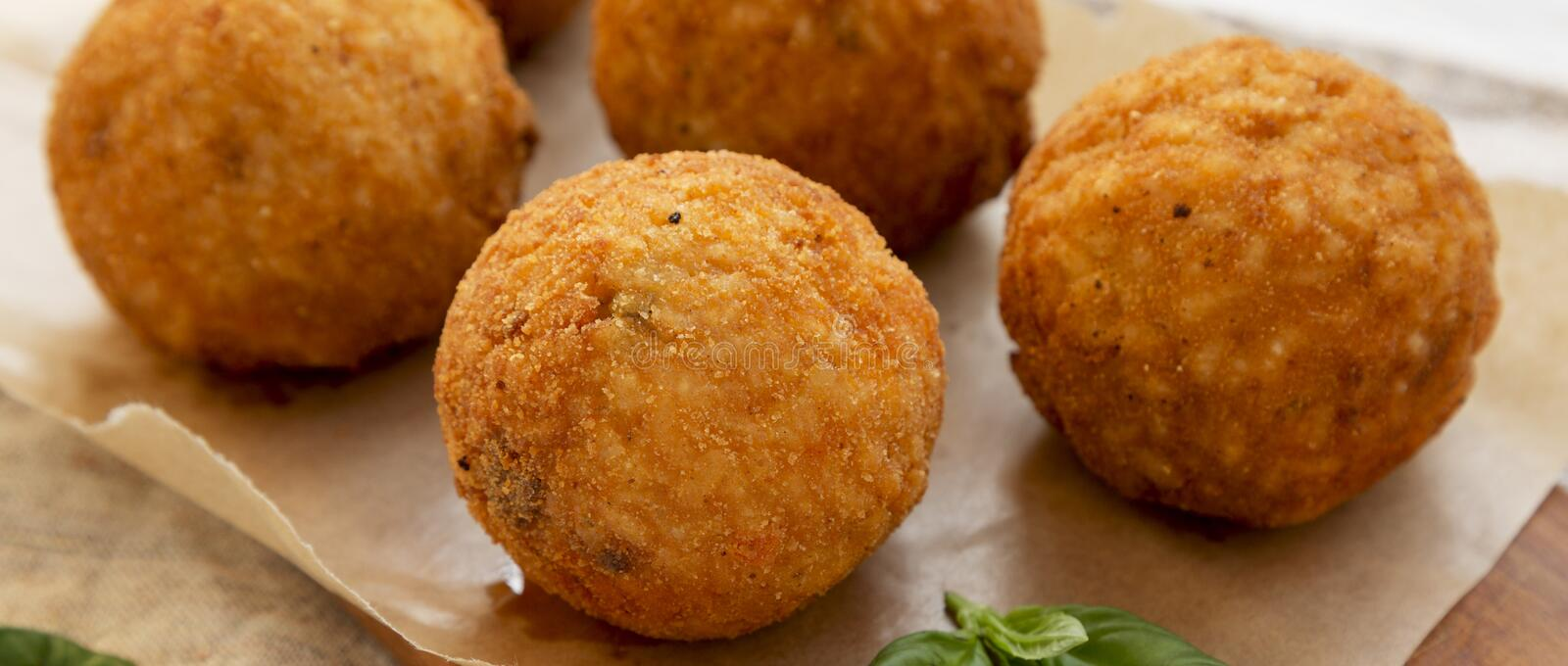 Homemade fried Arancini with basil on a rustic wooden board, low angle view. Italian rice balls. Closeup.  royalty free stock photography