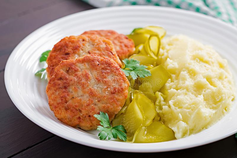 Homemade fried cutlets/meatballs with mashed potatoes and pickled cucumber. On white plate royalty free stock photos