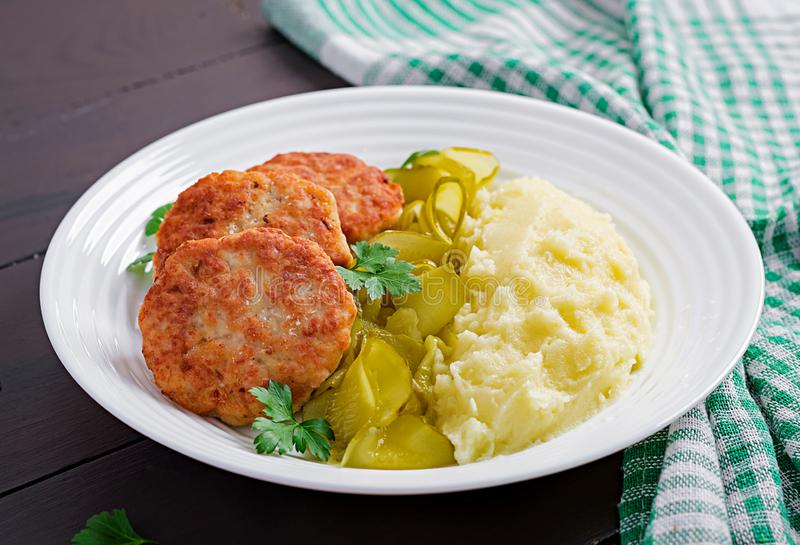 Homemade fried cutlets/meatballs with mashed potatoes and pickled cucumber. On white plate royalty free stock image