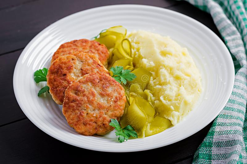 Homemade fried cutlets/meatballs with mashed potatoes and pickled cucumber. On white plate stock photography