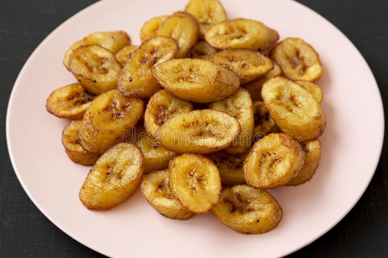 Homemade fried plantains on a pink plate on a black backgound, low angle view. Closeup.  royalty free stock photo