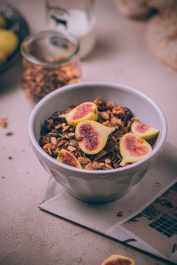 Homemade friska granola med färska fikon och honungsdrizzel i en frukostskål på rosa bord royaltyfri fotografi