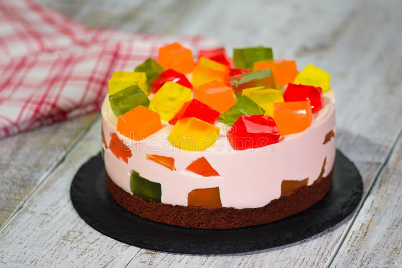 Homemade fruit dairy multi-colored jelly cake on a plate stock images
