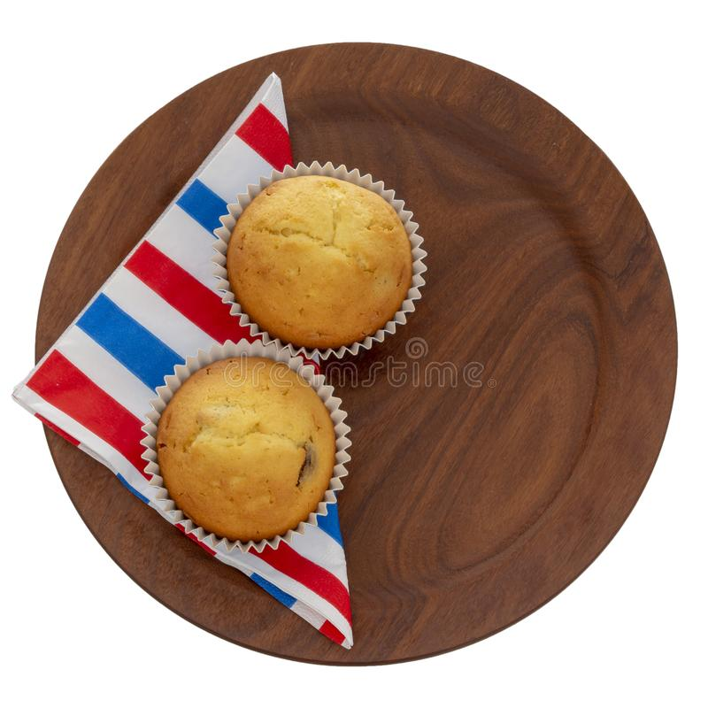 Homemade fruit muffins, cupcakes on red white and blue serviette, napkin on plate, isolated on white. Two small home. Homemade fruit muffins, cupcakes on red stock images