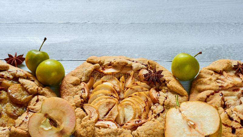 Homemade fruits tarts with chocolate topping on the concrete background. Vegetarian healthy autumn dessert - galette. With fresh plums and pears. Side view with stock images