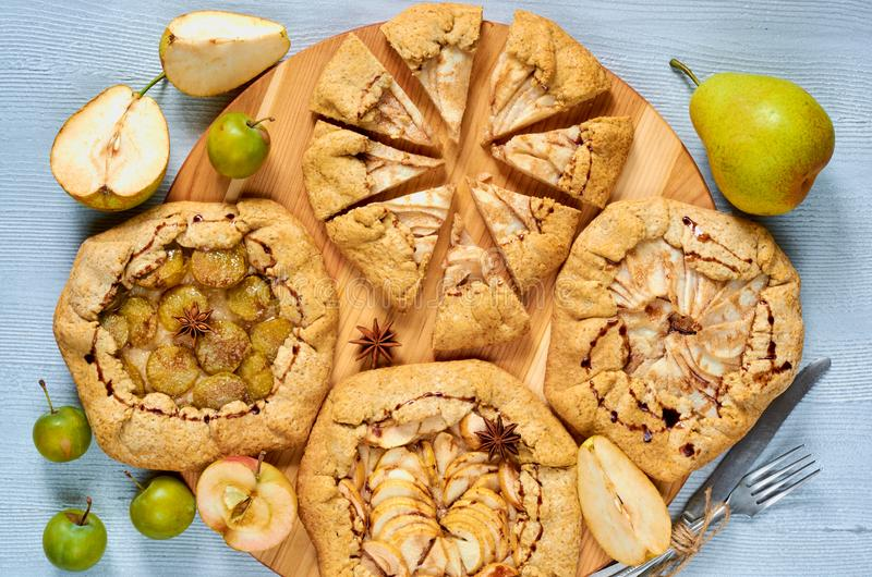 Homemade fruits tarts with chocolate topping decorated with vintage knife and fork on the concrete background. Vegetarian healthy autumn dessert - galette with royalty free stock photography
