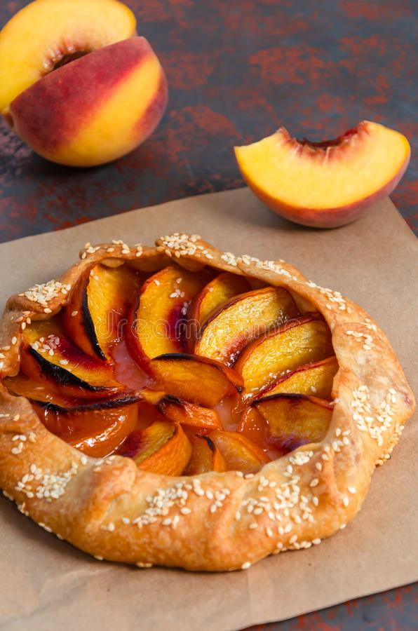 Homemade galette with peaches and sesame. Closeup of sweet summer fruit pie. Vegetarian dessert. Selective focus stock photography