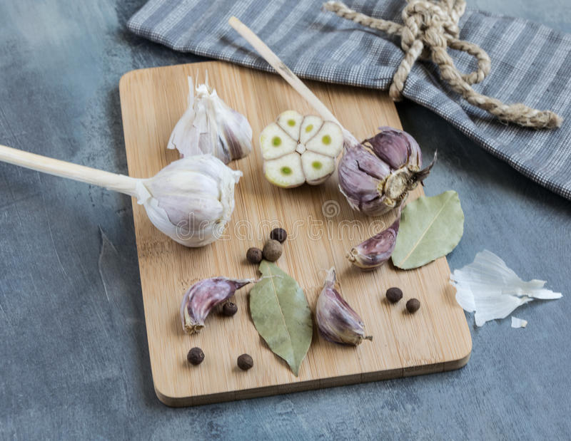 Homemade garlic with bay leaf and new spice placed on a wooden board and a cloth royalty free stock photos