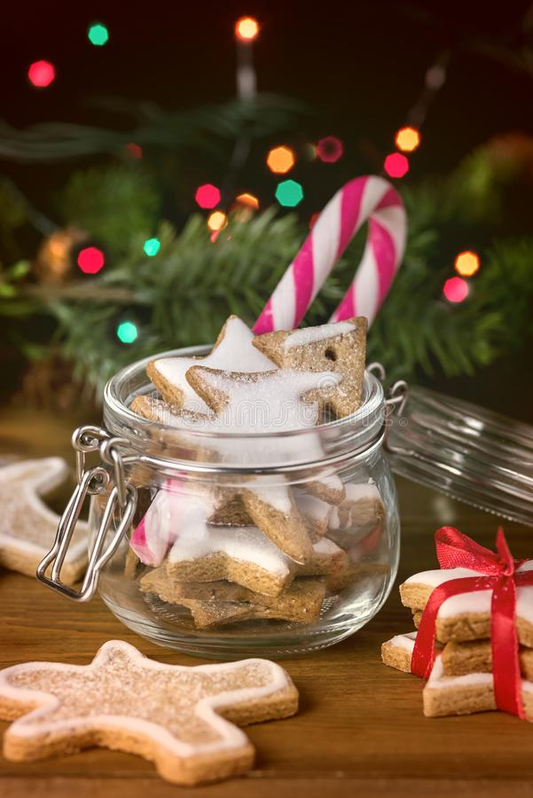 Homemade Gingerbread Biscuits in Glass Jar Christmas Background Holiday Festive Greeting Card Candy Cane Lights Wooden Background royalty free stock image