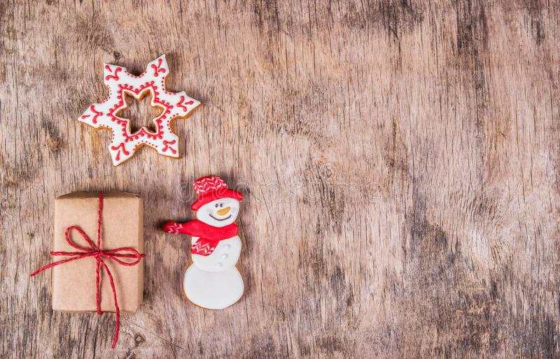 Homemade gingerbread cookie and gift box on wooden background. Handmade holiday sweets. Christmas cookies. Copy space. stock photos