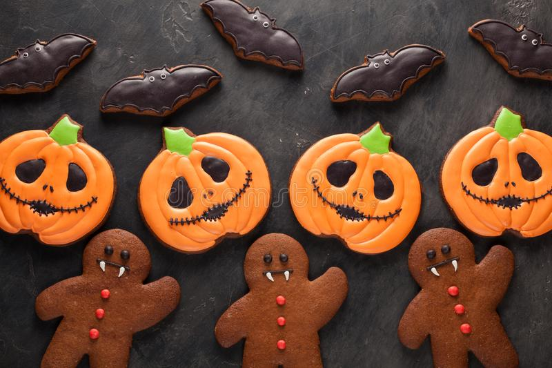 Homemade gingerbread cookies for Halloween in the form of pumpkins, gingerbread men and bats on dark concrete background. Top view royalty free stock photo