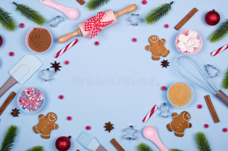 Homemade gingerbread cookies with ingredients for christmas baking and kitchen utensils on blue pastel background, royalty free stock photography