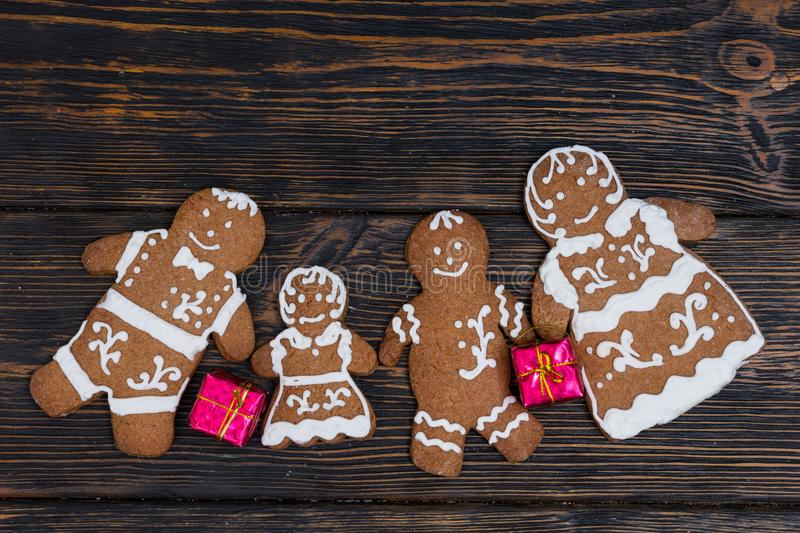 Homemade gingerbread family with small red gifts on dark wooden. Background. Mockup for seasonal offers and holiday post card royalty free stock photography