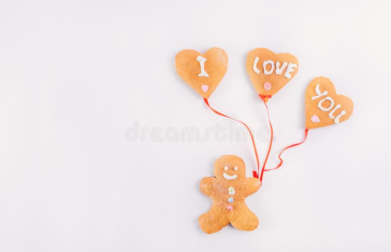 Homemade Gingerbread man with balloons in the shape of hearts with letteing I Love You on the white background. Valentines Day con. Cept. Gift for lover royalty free stock photography