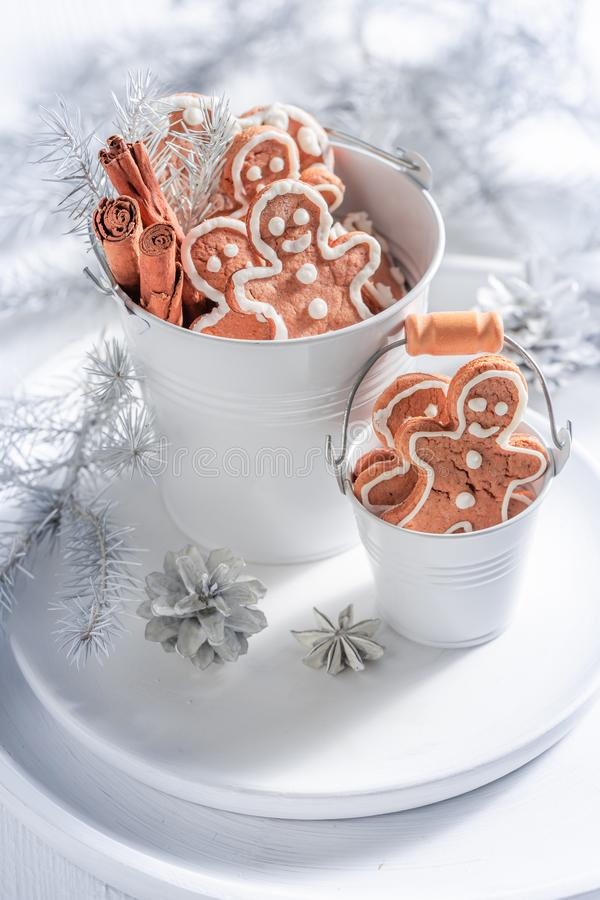 Homemade gingerbread man for Christmas in white bucket. On white table royalty free stock photo