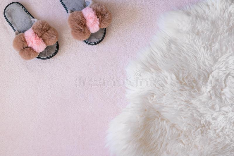 Homemade glamorous women`s slippers on a fluffy pink carpet with place for text. Copy space royalty free stock photography