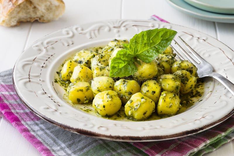 Portion of homemade gnocchi with `Pesto` sauce on white wooden table. Homemade gnocchi with `Pesto` sauce on white wooden table royalty free stock images