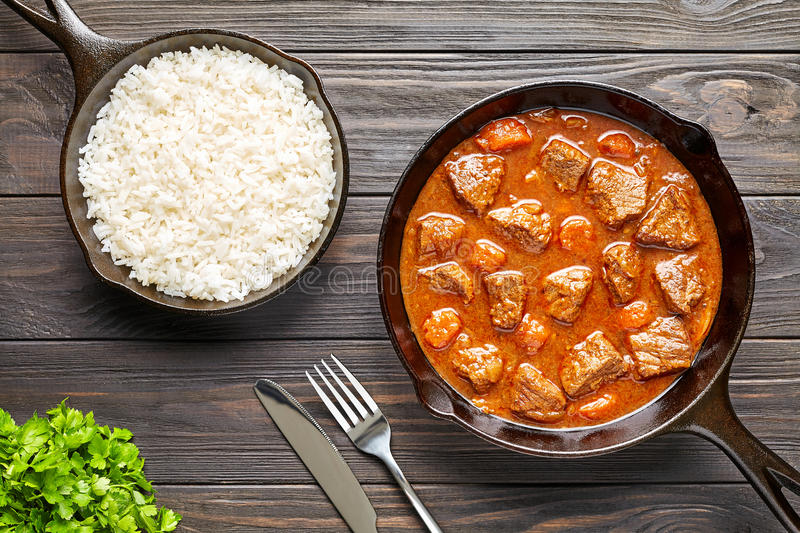 Homemade goulash traditional European beef meat stew soup spicy gravy food in cast iron pan with rice. And parsley on rustic vintage wooden table background stock photography
