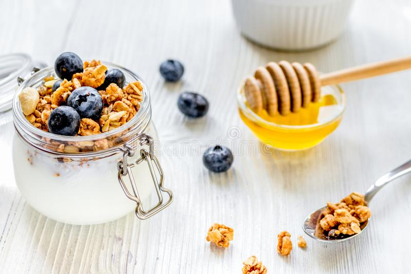 Homemade granola with blueberries in jar on white kitchen backgr. Homemade fitness granola with blueberries in jar on white kitchen table background royalty free stock photo
