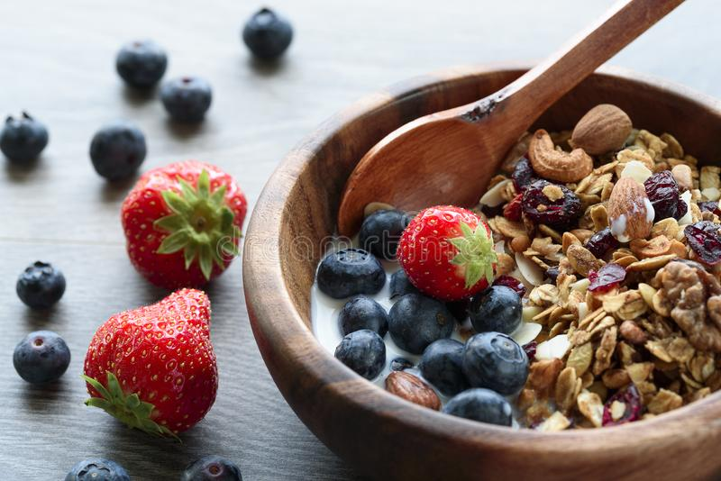 Homemade granola with fresh berry in wooden bowl.  stock image