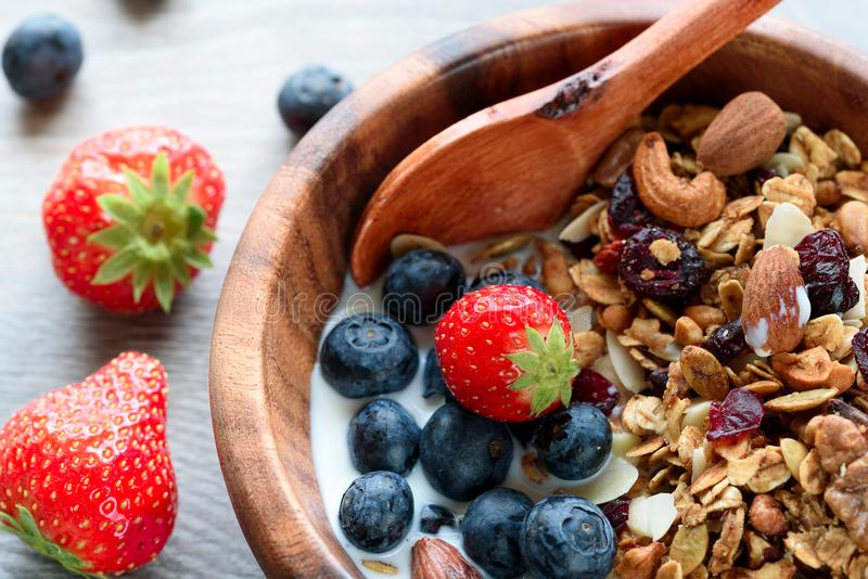 Homemade granola with fresh berry in wooden bowl.  stock images