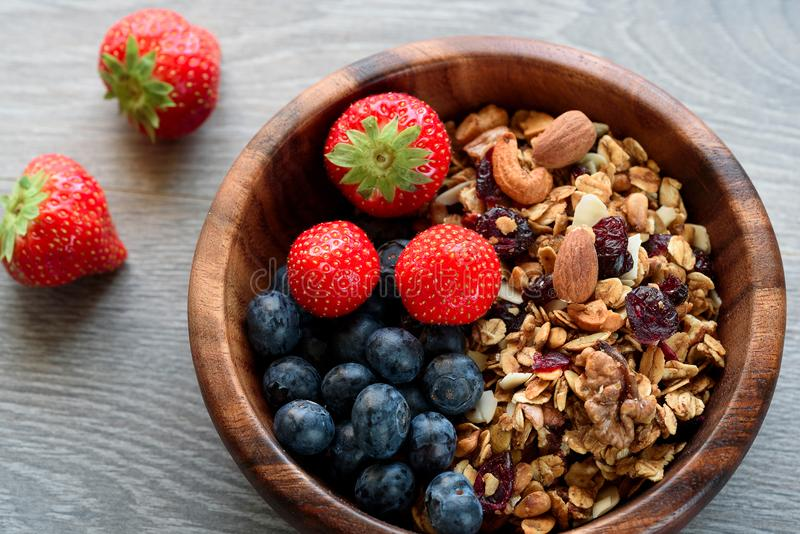 Homemade granola with fresh berry in wooden bowl.  royalty free stock image