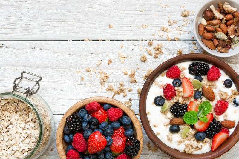 Homemade granola with greek yogurt, nuts and fresh berries in a bowl with cereal in ja. R for healthy breakfast over white wooden background. top view stock photos