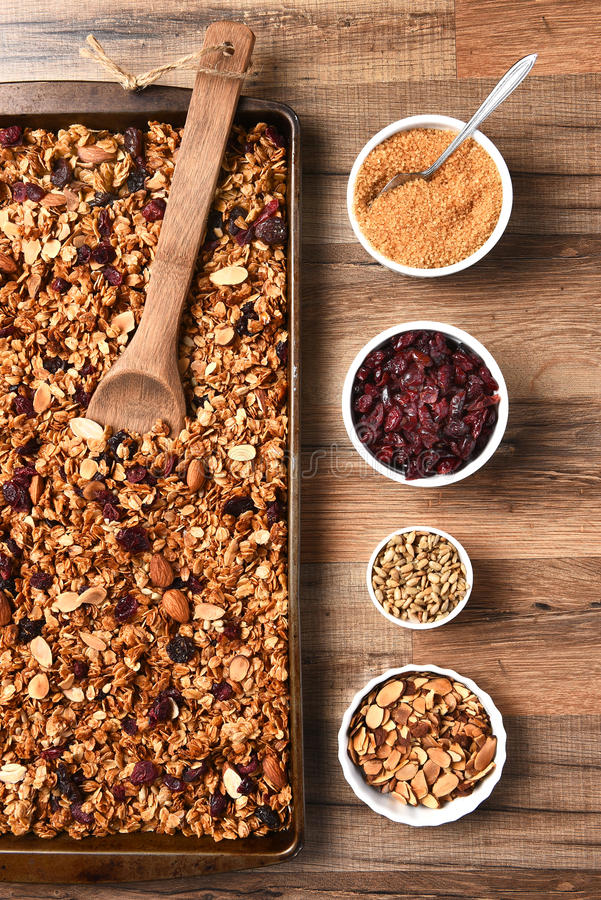 Homemade Granola. High angle view of fresh homemade granola. Baking sheet filled with the tasty, healthful food with containers of ingredients royalty free stock photography