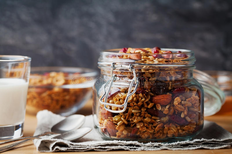Homemade granola in jar on rustic table, healthy breakfast of oatmeal muesli, nuts, seeds and dried fruit royalty free stock image