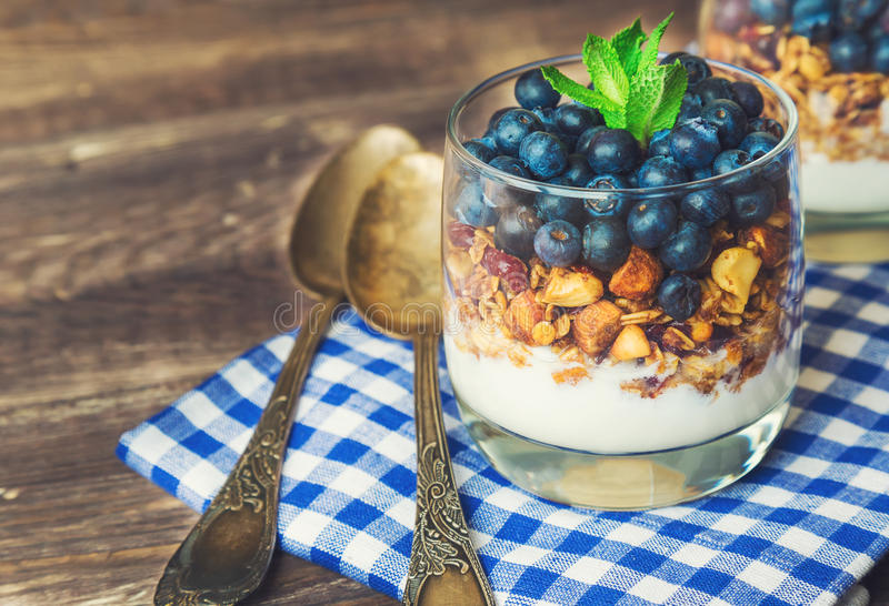 Homemade granola, muesli with blueberry and yogurt in glasses royalty free stock images