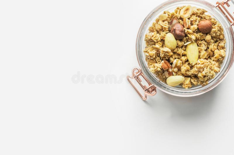 Homemade Granola Muesli with oats dried fruits coconut flakes hazelnuts almonds walnuts mixture in glass jar on white table stock photography