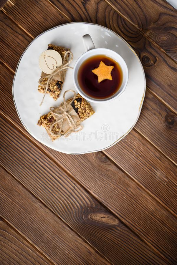 Homemade granola oatmeal energy bars, and cup of tea on white plate, healthy snack, copy space on wood desk royalty free stock photo