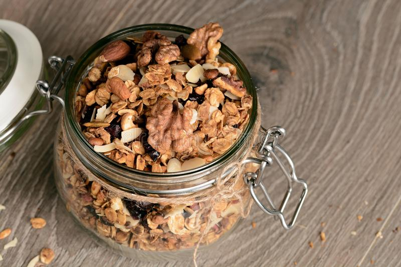 Homemade granola in open glass jar on rustic wooden background royalty free stock photography